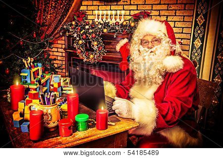 Modern Santa Claus sitting with a laptop at his home. Christmas.