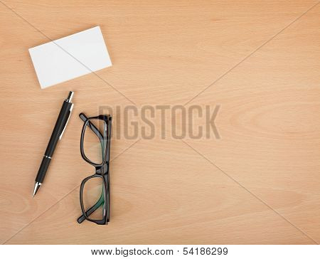 Blank business cards with pen and glasses on wooden office table with copy space