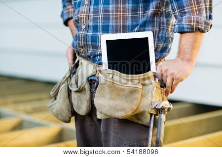 Midsection of construction worker with tablet computer in toolbelt at site