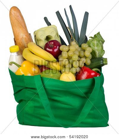 Groceries in green bag isolated on white background