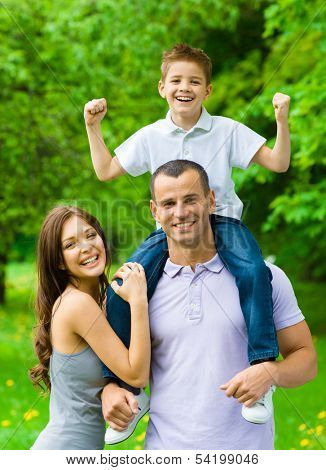 Happy family of three. Dad keeps son on shoulders. Concept of happy family relations and carefree leisure time