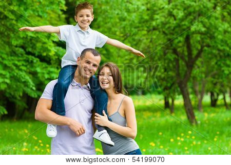 Happy family of three. Father keeps son airplane gesturing on shoulders. Concept of happy family relations and carefree leisure time