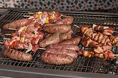 stock photo of brazier  - brazier with sausages and steak on grill - JPG