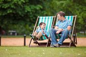image of kensington  - Happy father and son having rest in city park on beautiful summer day - JPG