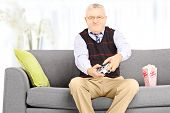 image of indoor games  - Senior man seated on a couch playing video games at home - JPG