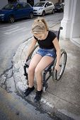 picture of lame  - A girl in a wheelchair on the sidewalk or pavement trying to cross the road - JPG