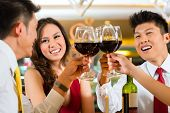 foto of chinese restaurant  - Two Asian Chinese Couples or friends or business people toasting during dinner or lunch in a elegant restaurant with red wine glasses - JPG