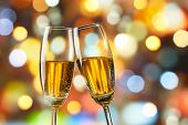 image of flute  - two glasses of champagne toasting against bokeh lights background - JPG