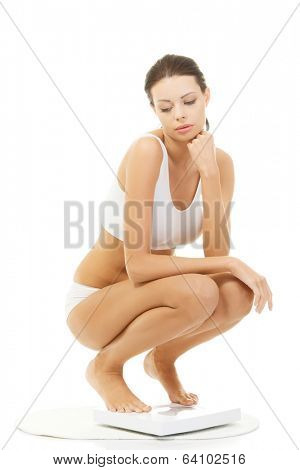 Frustrated woman on scale, isolated on white
