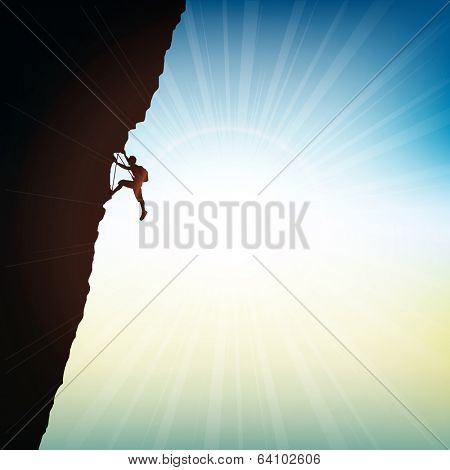 Silhouette of an extreme rock climber against a sunny sky