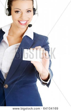 Smiling customer service representative with headset holding a blank empty businesscard. Isolated on white background.