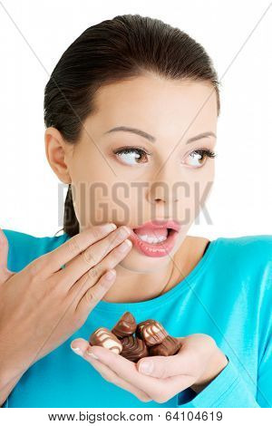 Embarrassment beautiful woman with hand full of chocolates