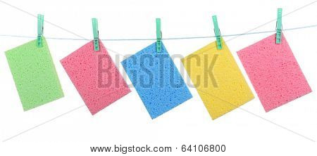 Kitchen sponges hanging on rope isolated on white