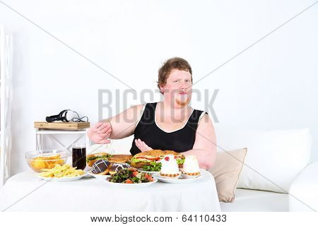 Fat man  do not want to eat a lot of unhealthy food, on home interior background