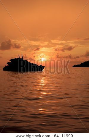 Luxury Yacht and island on ocean at sunset
