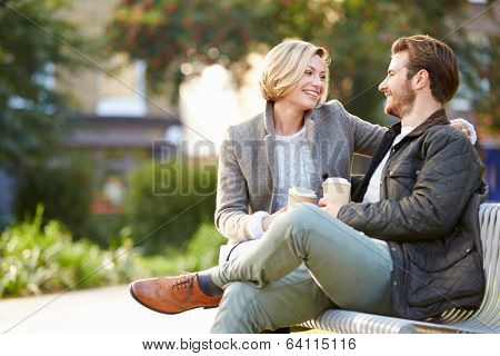 Couple Relaxing On Park Bench With Takeaway Coffee