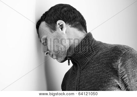 Sad Young Caucasian Man Rested His Head On White Wall