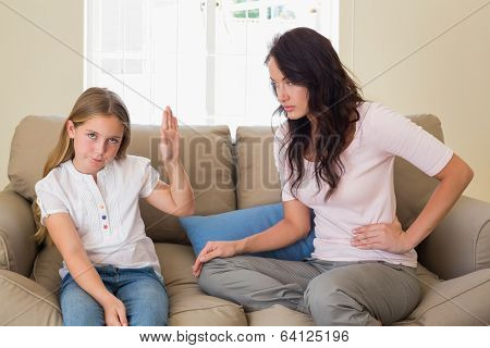 Stubborn girl showing stop gesture to mother while sitting on sofa at home