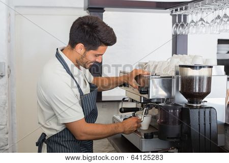 Side view of a smiling young waiter making cup of coffee at coffee shop