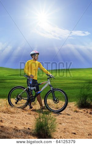 Young Man Standing Beside Moutain Bike ,mtb On Hill With Sun Shining On Blue Sky Use For Sport Leisu
