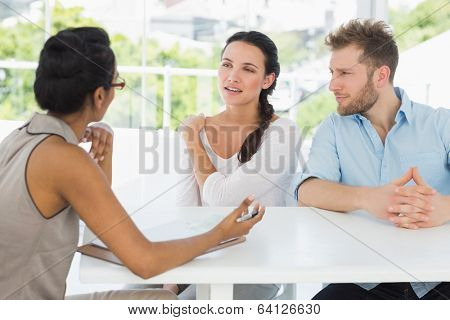 Therapist talking with couple sitting at desk in therapists office
