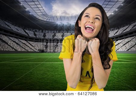 Excited football fan in brasil tshirt in a vast football stadium with fans in white