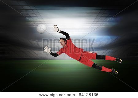 Fit goal keeper jumping up in a large football stadium with lights