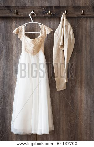 Bridesmaid dress and cardigan hanging from hooks