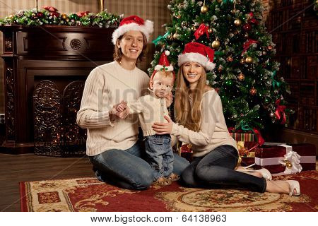 Happy smiling young family near the Christmas tree celebrate New Year. Mom dad and kid at Christmas tree. Mother father and child on Christmas Eve. Mummy, Daddy and Baby.