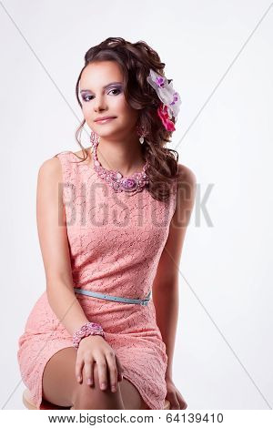 Cute Girl With Flowers In Her Hair In A Pink Dress Is Smiling