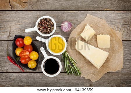 Parmesan cheese, tomatoes, herbs and spices on wooden table background