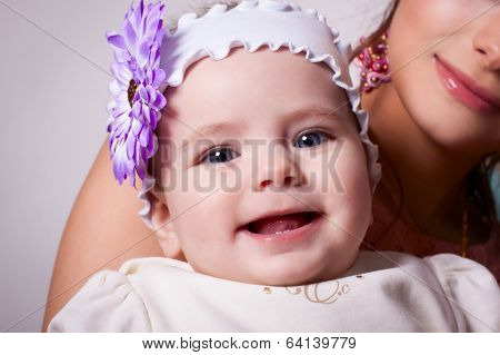 6 Months Baby Girl Smiling With A Flower On Her Head