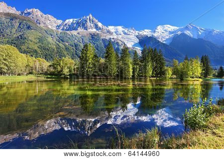 Snowy mountains and evergreen spruce reflected in the lake. City park in the mountain resort of Chamonix in France