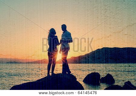 Young couple talking to a rock by the sea at the setting sun. Filtered image: vintage, grunge and texture effects