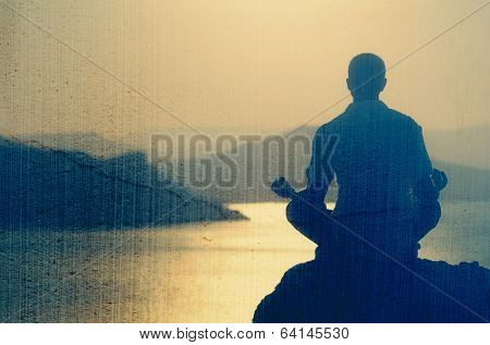Guy meditating at sunset sitting on a rock by the sea. Filtered image: vintage, grunge and texture effects