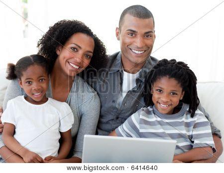 Familia afroamericana feliz usando una computadora portátil en la sala de estar