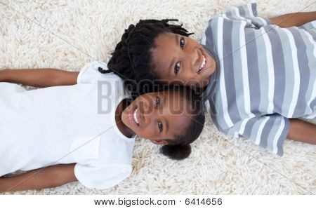 Brother And Sister On Floor With Heads Together
