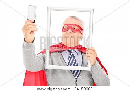 Mature superhero taking a selfie with a picture frame isolated on white background