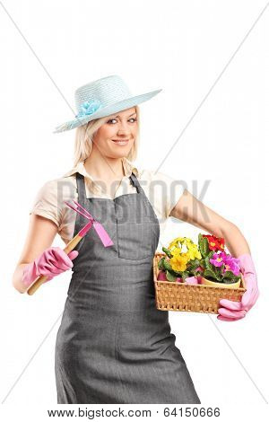 Female gardener holding a mattock and a basket with flowers isolated on white background