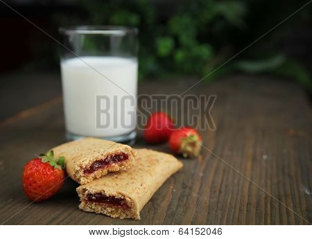Organic cereal bar with fruit filling and fresh raspberry on a wooden table with a glass of milk