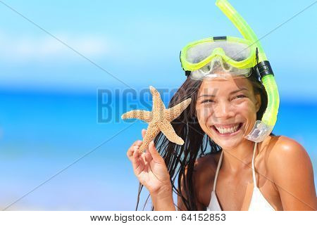 Beach travel people - woman with snorkel and starfish in bikini enjoying summer vacation holidays on tropical resort by ocean sea. Beautiful young mixed race Asian Caucasian woman smiling happy.