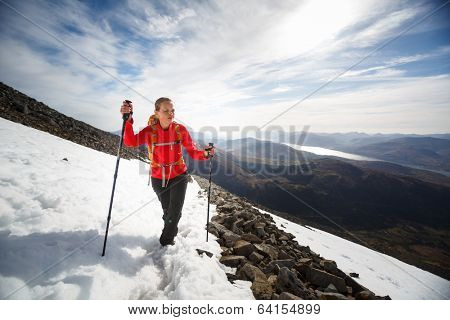 Pretty, young female hiker going uphill, crossing a snow field