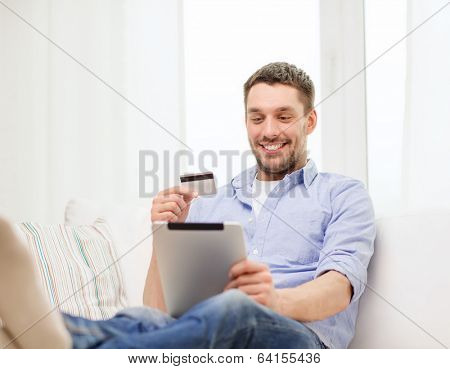 technology, home and lifestyle concept - smiling man working with tablet pc computer and credit card at home