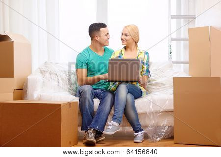 moving, home, technology and couple concept - smiling couple relaxing on sofa with laptop in new home