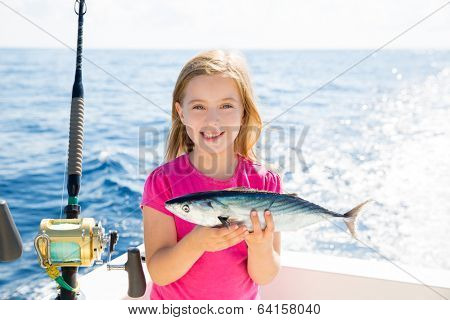 Blond kid girl fishing tuna bonito sarda fish happy with trolling catch on boat deck