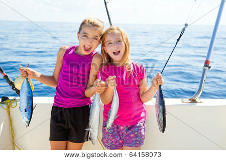 Happy tuna fisherwomen kid girls on boat with fishes trolling catch