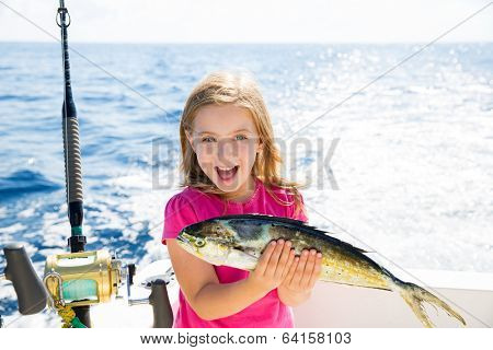 Blond kid girl fishing Dorado Mahi-mahi fish happy with trolling catch on boat deck