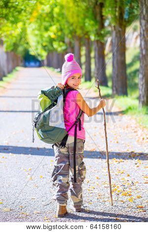 hiking kid girl with walking stick and backpack exploring autumn track and camouflage pants