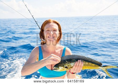 Woman fishing Dorado Mahi-mahi fish happy with trolling catch on boat deck