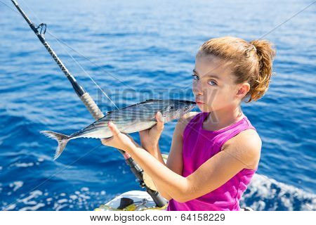 kid girl fishing tuna bonito sarda kissing fish for release due little size
